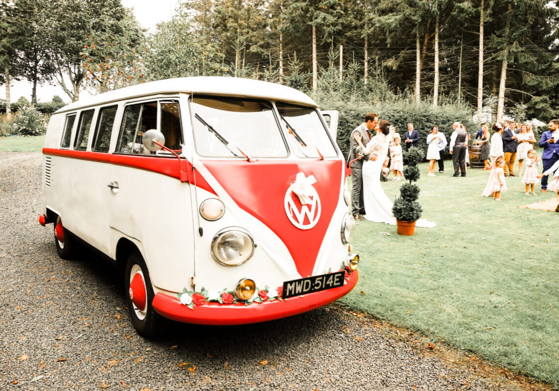 VW Wedding Splitscreen Camper Van with Bride and Groom Kissing